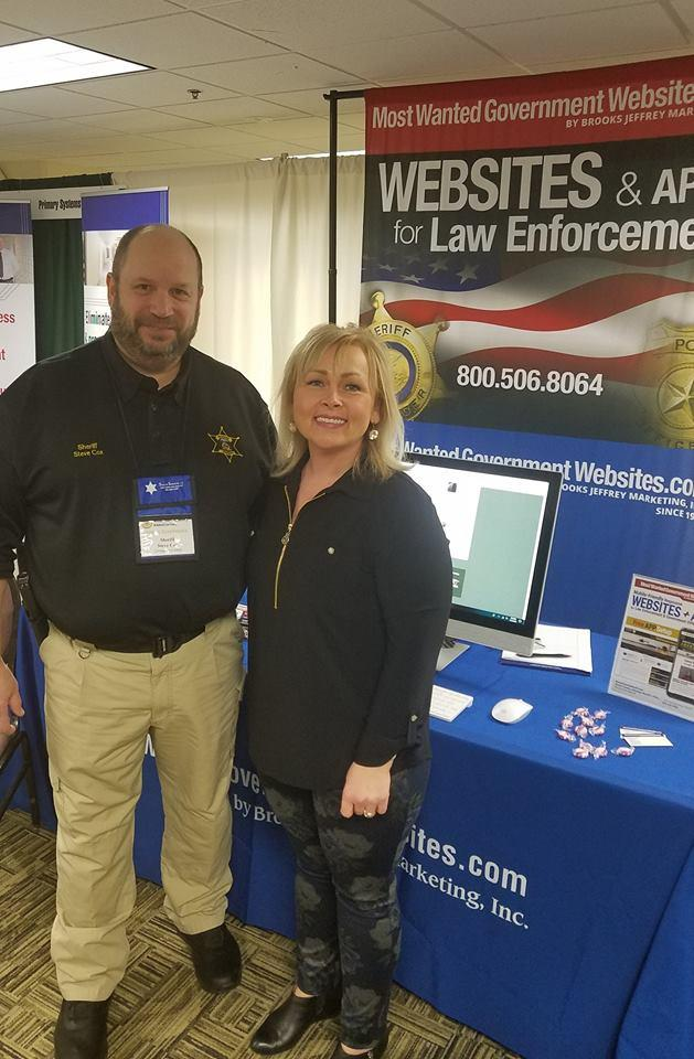 Renea standing at her booth next to a Missouri Sheriff