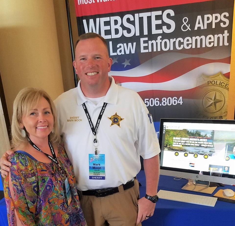 Renea and Sheriff Moon in front of trade show booth